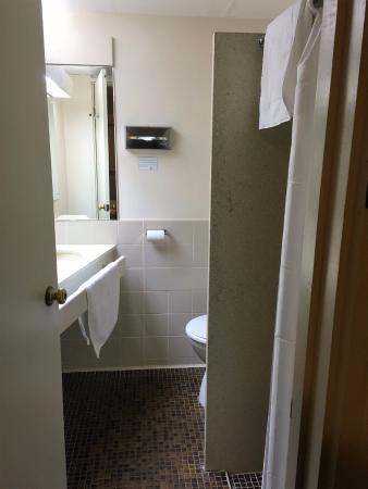 Adelaide Meridien Hotel & Apartments: Small brown tired tiles and stained basin. Shower curtain