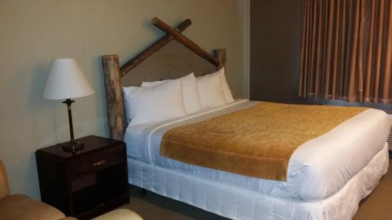 Rawlins, WY: King room with 3 sheet top of bed and log headboard