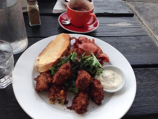 Toukley, ออสเตรเลีย: Corn fritters with avocado smash, roasted capsicum, rocket, bacon, toast and sour cream dip.