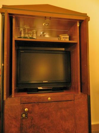 A cupboard with flat TV and the mini bar - Picture of NH