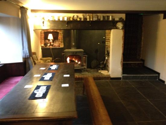 The Holman Clavel Inn: A Large eating table next to a warm fire