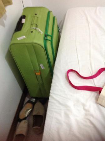 Espaço entre a cama de casal e janela que dá vista para lavanderia do hotel.
