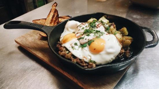 ปรินซ์จอร์จ, แคนาดา: DUCK CONFIT HASH, pesto hashbrowns, two sunny side eggs topped with spiced cilantro yogurt and d