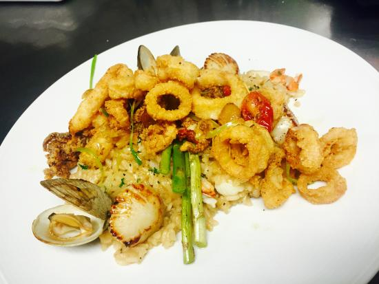 Warwick, RI: Fresh lobster risotto paired with clams and scallops . Finished with crispy calamari , shaved le