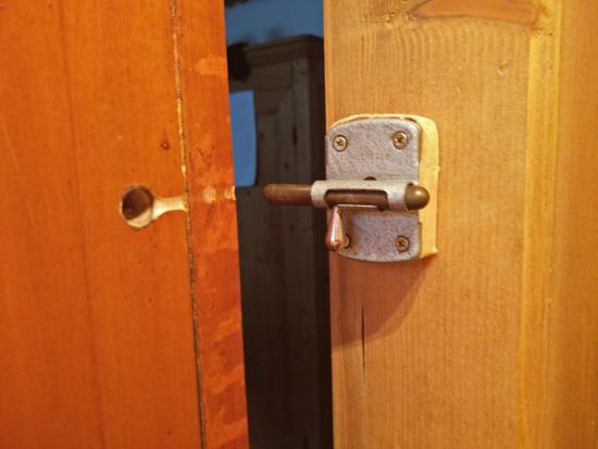 Chalet Neve : The door lock, which is only held on with one loose wood screw.