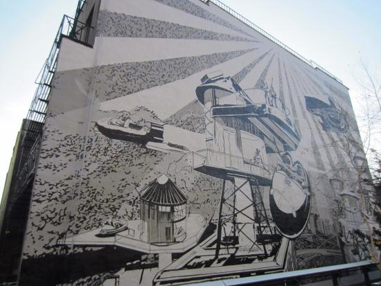 A mural on the side of a building lining the elevated for Construction mural