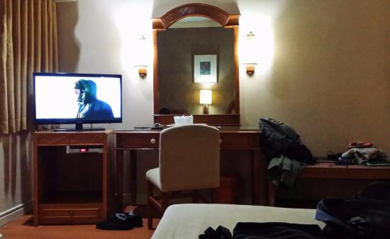 dimly lit room led tv and dresser picture of the grand city hotel rh tripadvisor com