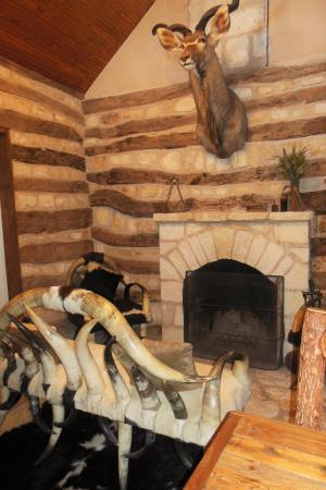 Living room, complete with fireplace, cowhide rug, and furniture made of longhorns and hide
