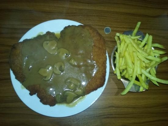 Bad Friedrichshall, Tyskland: Full-Size Schnitzel. The coin in the picture is the size of a quarter.