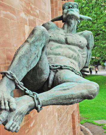 Coventry, UK: The devil laying prone defeated outside the wall of the church