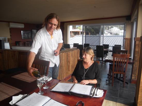 Гордонз-Бей, Южная Африка: Greg pours wine for Brigid at Harbour Lights whilst we study the menu.
