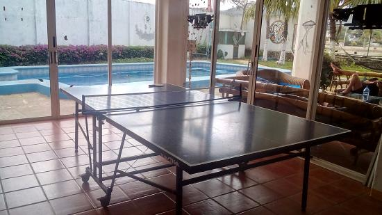 Yajure Surf Hostel : Table tennis, with the swimming pool and outside area on the background