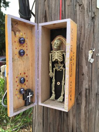 A tiny skeleton in a box on a telephone pole  - Picture of Village