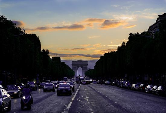 Paryż, Francja: Looking down Champs-Elysees towards the Arc de Triomphe at sunset