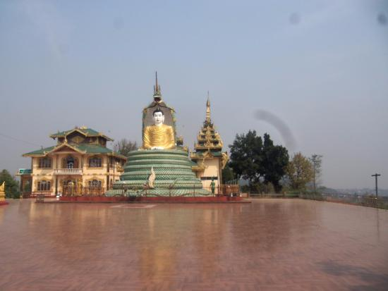 Lashio, Birma: The giant Buddha in the temple grounds showing the Buddha sitting on the coiled snake.