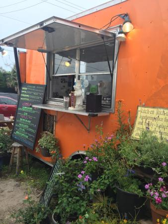 Sweet little garden frames a bright orange food truck - Picture of ...