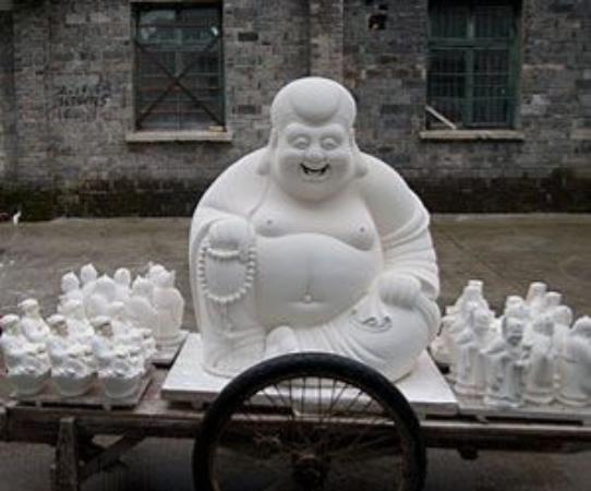 Jingdezhen, Çin: The Unfired Laughing Buddha is delivering to the kiln.