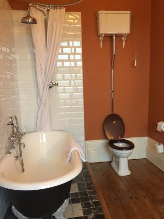 75e785a33f Moy House  A claw foot bathtub and a toilet with the tank overhead and a