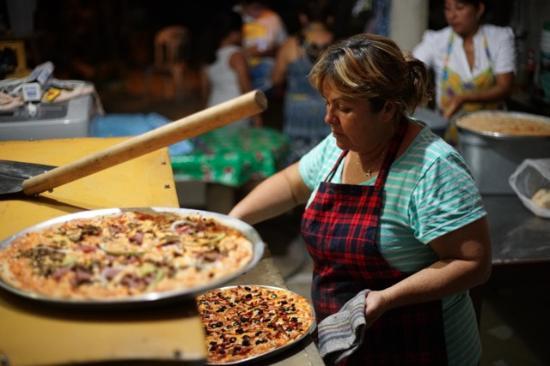 Dzilam de Bravo, México: It's a family operation at Pizzeria Los Gemelos.  Here Tia Sandra checks the pizzas.