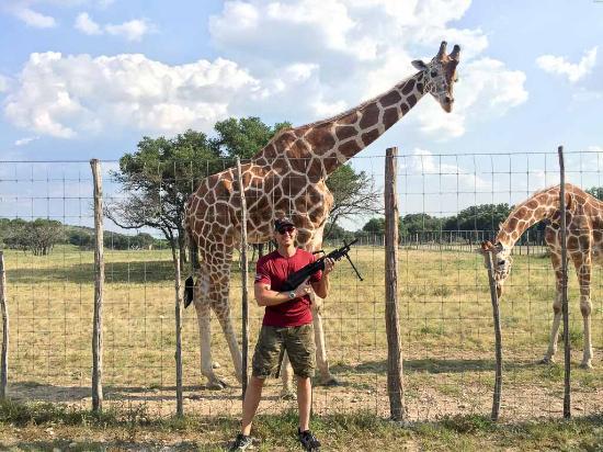 Uvalde, TX: Guest with his Saw machine gun next to giraffes.