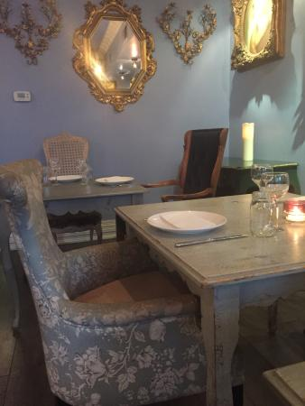 Mismatched antique looking chairs tables art work an eclectic