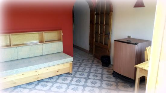 Einblick in ein Wohnzimmer mit Tisch, Couch, Kühlschrank und Tür zum ...