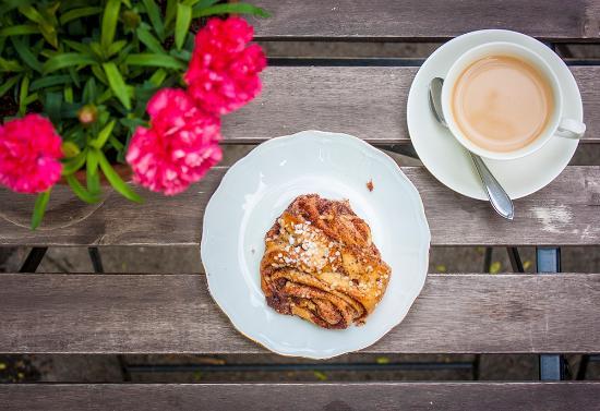 Kahvi ja uunituore korvapuusti kukkien keksellä Cafe Antiquen sisäpihalla<3