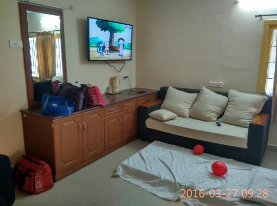"""TTDC Hotel: The room with 40"""" TV, Sofa, Double bed and storage space."""