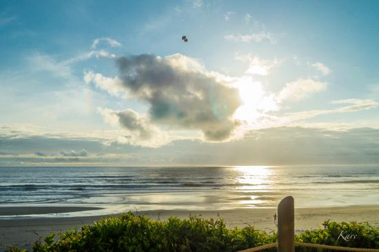 Pelican Shores Inn: As the sun begins to set a man flies a kite in front of the clouds