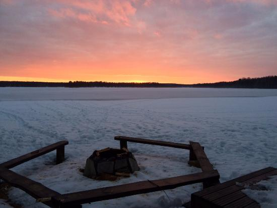 Rautavaara, Finland: A beautiful sunset from the beach across the frozen lake!