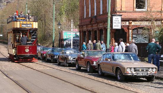 Matlock, UK: Open top tram drives passed a line of parked Jensen cars