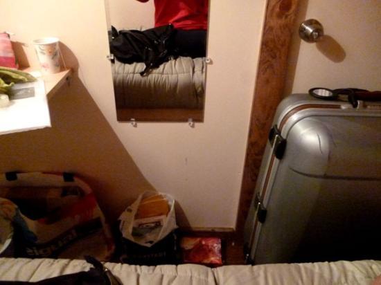 East Village Suites: Der geschlossene Koffer versperrt die Türe, so eng ist die (oben offene/vergitterte) Box