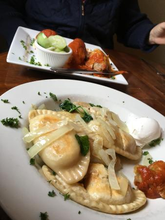 European Cafe: Six pierogis with stuffed cabbage in background.