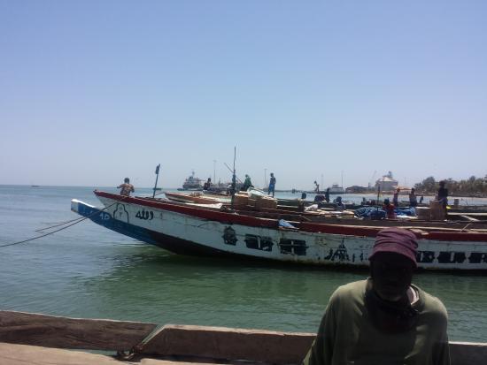 Central River Division, Gambia: Een oversteek van de Gambia rivier in een houten boot boven op de cargo