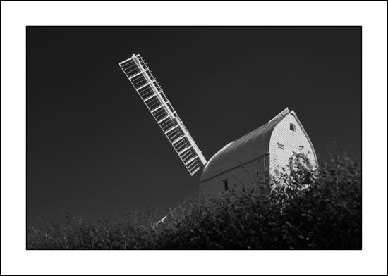 Hassocks, UK: Black & white image of Jill Mill looking over the hedge from the car park