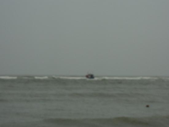 small fishing boat breaking thru the surf line - Picture of