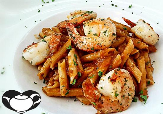 penne pasta in neopolitan sauce topped with garlic shrimp at