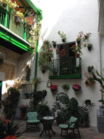 Apartamentos Jerez: Flowered courtyard with seating areas