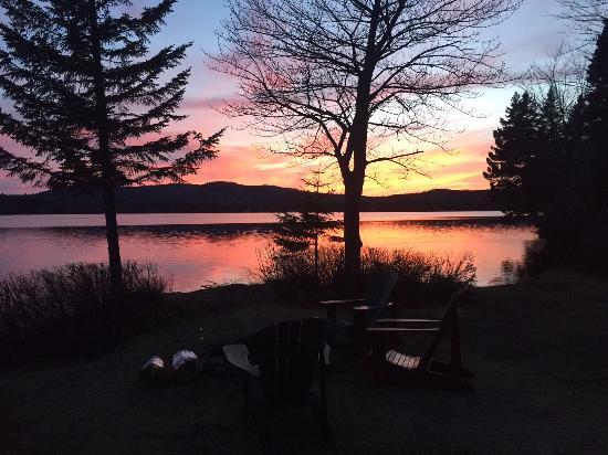 تول تيمبر لودج: A sunset view in late April 2016 outside of the lake side cabins.