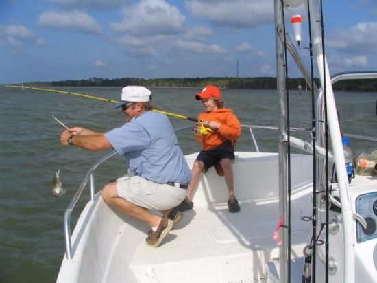 Apalachicola, Floryda: Captain Dwayne helping JP with a fish....he's wearing all Clemson stuff & is now a Junior at Cle