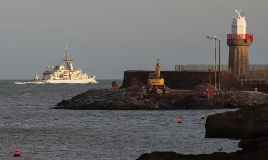Dunmore East, Irlandia: View from The Strand Inn towards lighthouse and navy ship.