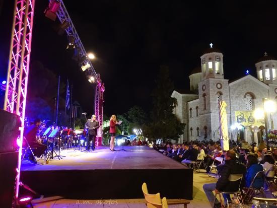 Paiania, Yunani: δεξιά ο Ι.Ν. Ζωοδόχου Πηγής και αριστερά η σκηνή από συναυλία της Φιλαρμονικής της Παιανίας