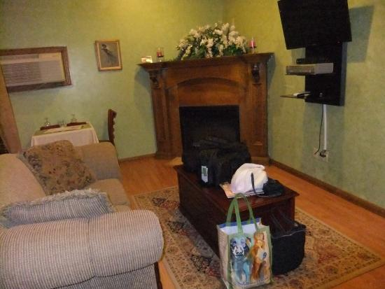 Whispering Pines Bed and Breakfast: The sitting area with the TV and cozy fireplace.