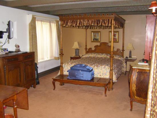 Sutter Creek Inn: Sturdy four poster bed viewed from seating area.