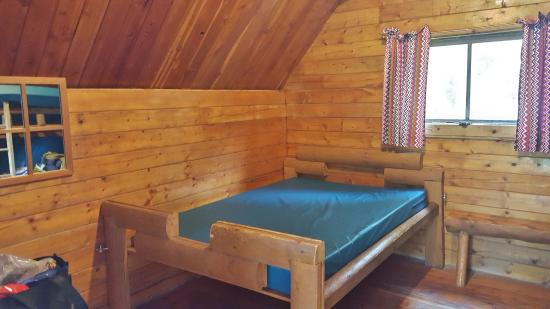 Sallisaw, OK: Full bed inside cabin #1 with a view of the bunkbeds in the mirror