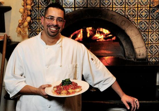 Rosalie's Cucina: Executive Chef, Marc Albino, standing in front of the imported Italian pizza oven.