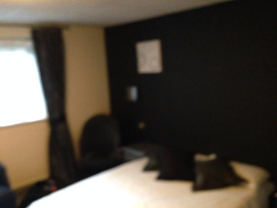 Himley, UK: Black wall, covered in white stains - no headboard, dirty cushions, two very very thin pillows