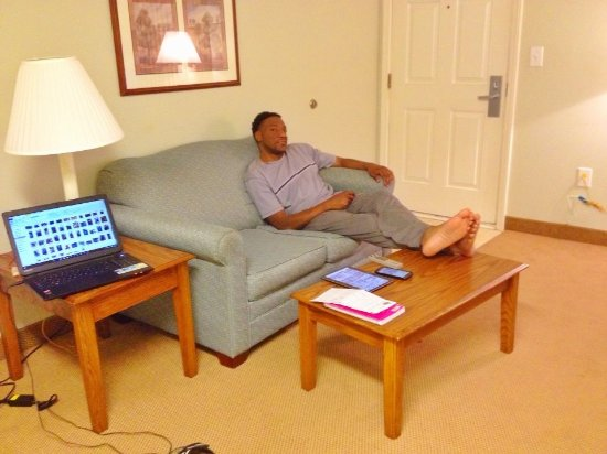 Affordable Suites of America, Greenville: Michael relaxing after a crazy day with the relatives. Couch is so comfy.