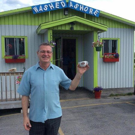 Washed Ashore Antiques & Coffee Bar: The owner, Kirk, posing with a coffee cup all the way from Colombia!