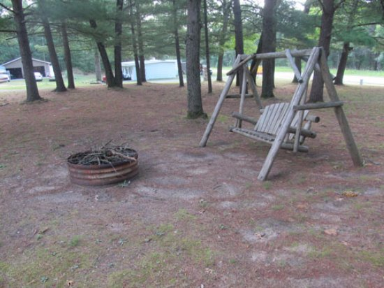 Baldwin, MI: fire pit and porch swing in front outside of cabin